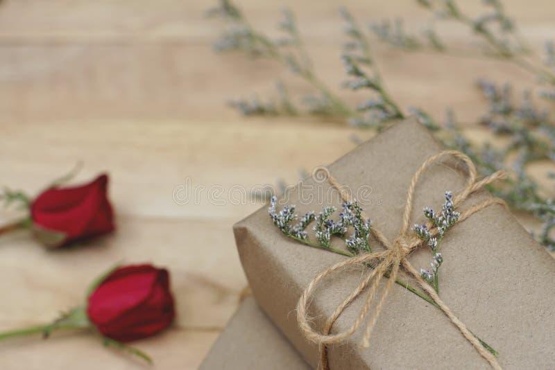 Presente envuelto en papel marrón amistoso de la caja de regalo de Eco adornado con la rosa y otras flores en el fondo de madera, fotos de archivo