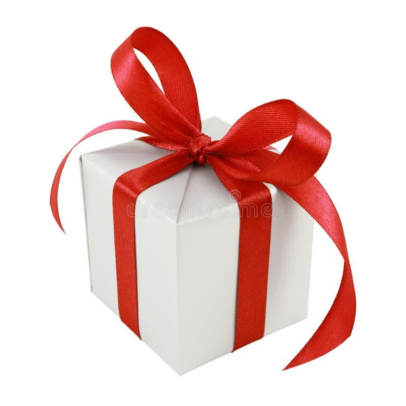 Presente envuelto regalo de plata con el arqueamiento rojo del satén imagenes de archivo