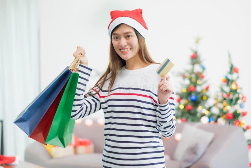 Presente feliz do Natal da compra do cartão de crédito do uso da mulher de Ásia na compra fotografia de stock