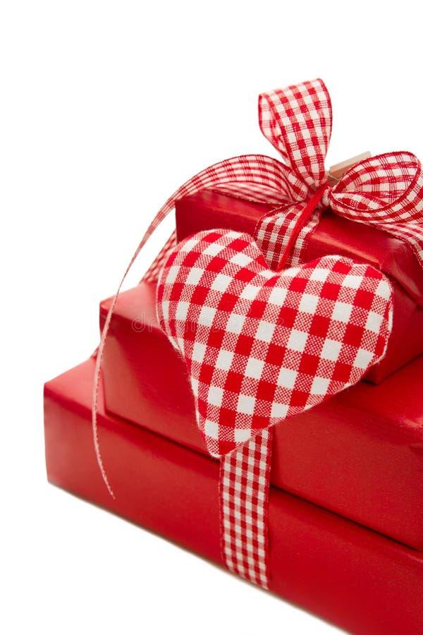 Presente isolati avvolti in carta rossa con un cuore controllato immagine stock libera da diritti