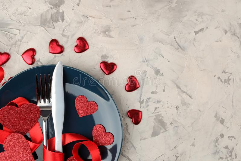Presente la configuración Placa azul con un cuchillo y una bifurcación y corazones rojos en un fondo del cemento ligero Día del ` imagen de archivo