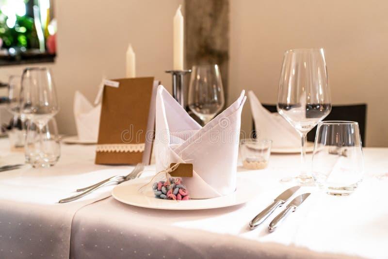 Presente la disposición en las huéspedes que esperan de la boda para con las flores del agua de los platos imagen de archivo