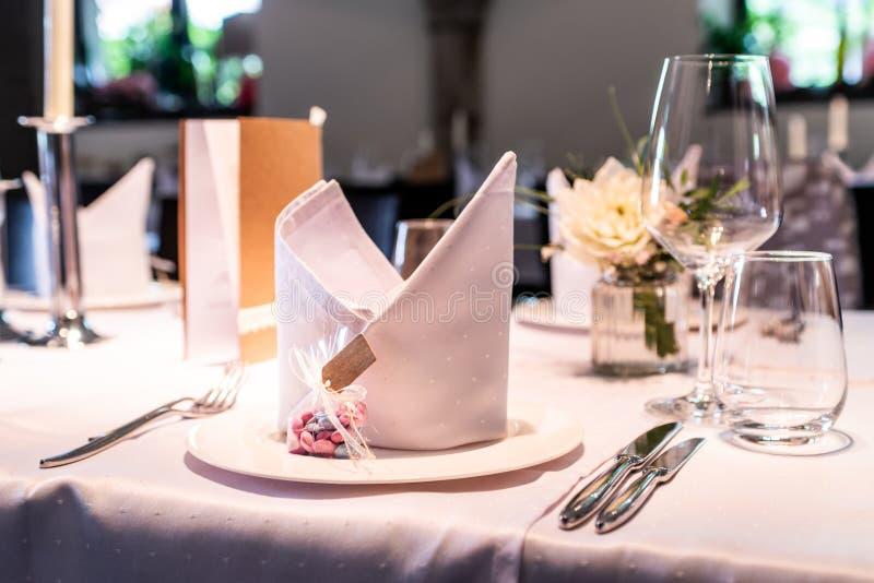 Presente la disposición en las huéspedes que esperan de la boda para con las flores del agua de los platos foto de archivo