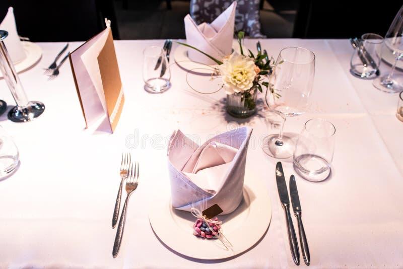 Presente la disposición en las huéspedes que esperan de la boda para con las flores del agua de los platos fotos de archivo libres de regalías