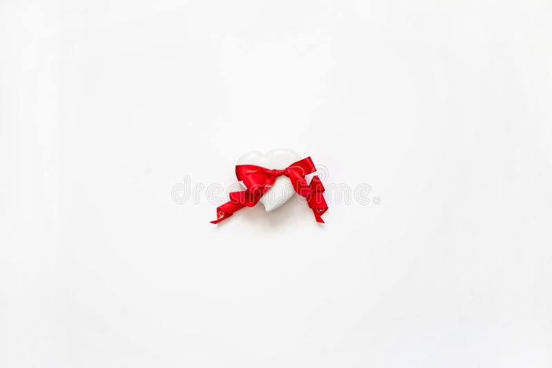 Presente luxuoso para o dia do ` s do Valentim Caixa branca na forma de um coração amarrado com uma fita vermelha em um fundo bra foto de stock royalty free