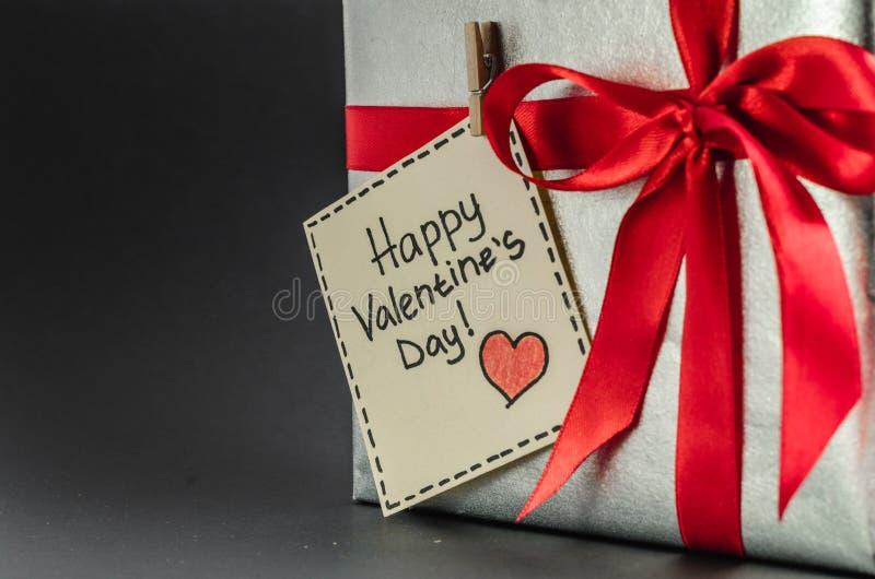 Presente na prata que empacota com fita vermelha e cumprimentos com dia do ` s do Valentim fotografia de stock
