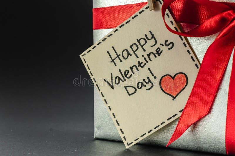Presente na prata que empacota com fita vermelha e cumprimentos com dia do ` s do Valentim imagens de stock