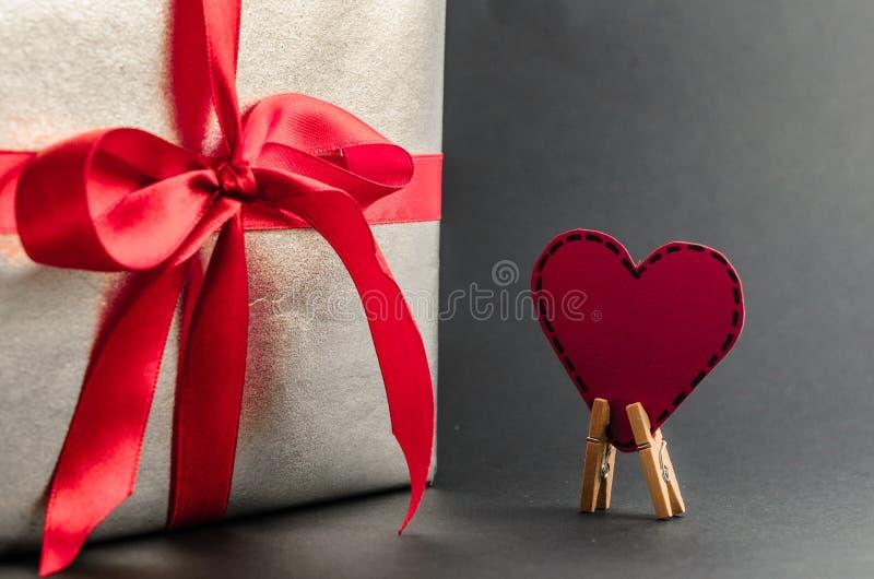 Presente na prata que empacota com fita vermelha e cumprimentos com dia do ` s do Valentim imagem de stock