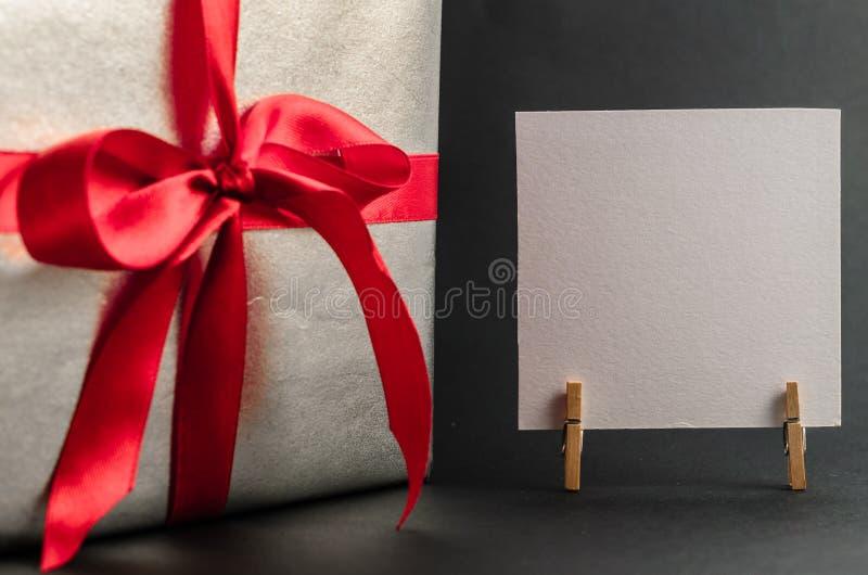Presente na prata que empacota com fita vermelha e cumprimentos com dia do ` s do Valentim com espaço livre para o texto imagem de stock royalty free