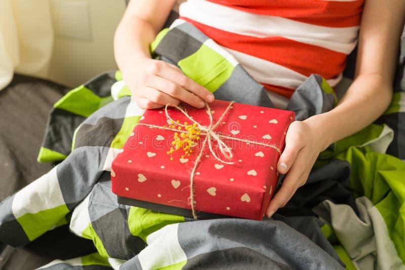 Presente nas mãos Embalado em crafting o papel com os corações vermelhos, decorados com um ramo da mimosa amarela floresce fotografia de stock royalty free