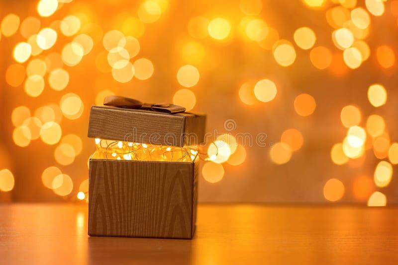 Presente no fundo obscuro das luzes do ano novo fotografia de stock