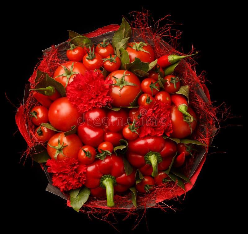 Presente original feito a mão sob a forma de consistir do ramalhete tomates, pimentas vermelhas, folhas de louro em um fundo pret foto de stock