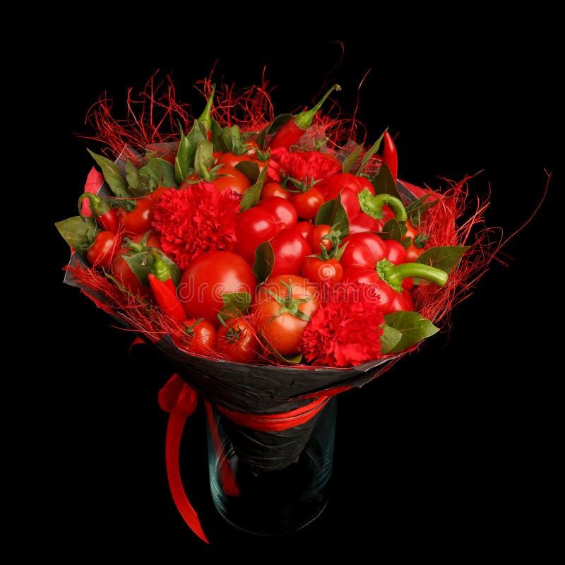 Presente original feito a mão sob a forma de consistir do ramalhete tomates, pimentas vermelhas, folhas de louro que estão em um  foto de stock