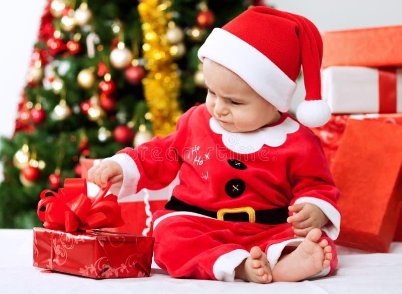 Presente pequeno bonito da abertura de Santa do bebê para o Natal foto de stock