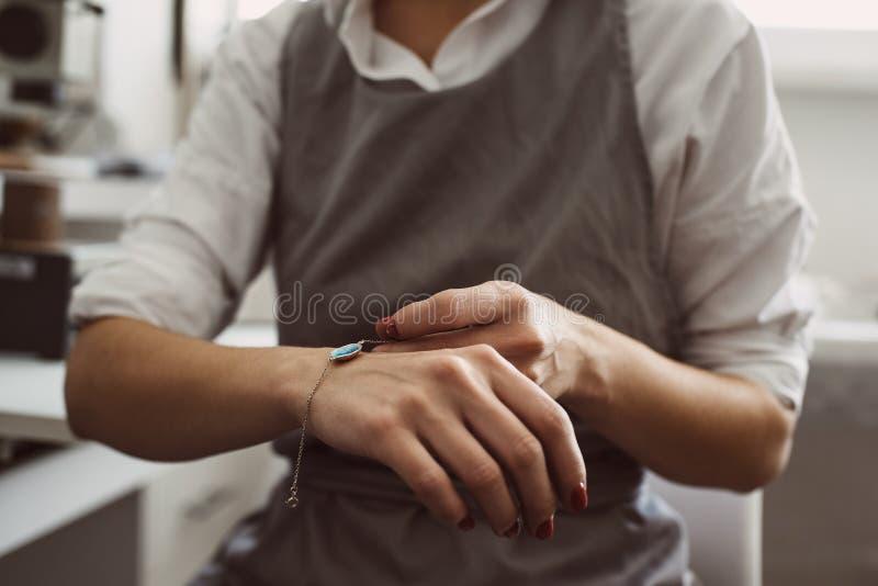 Presente perfeito Retrato do bracelete de prata vestindo do joalheiro fêmea ao trabalhar em sua oficina da joia imagens de stock royalty free