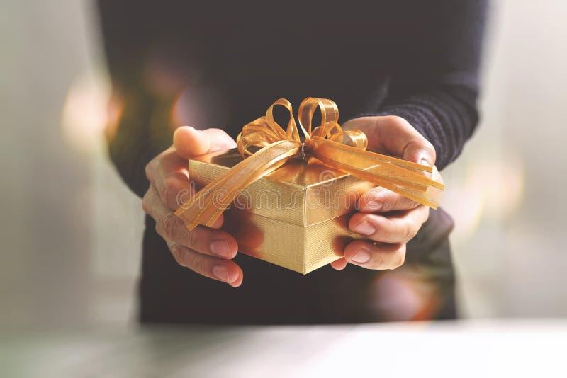 presente que dá, mão do homem que guarda uma caixa de presente em um gesto da doação B fotos de stock