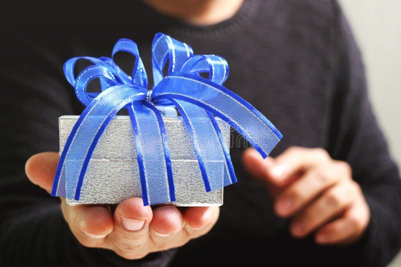 presente que dá, mão do homem que guarda uma caixa de presente em um gesto da doação B imagens de stock royalty free
