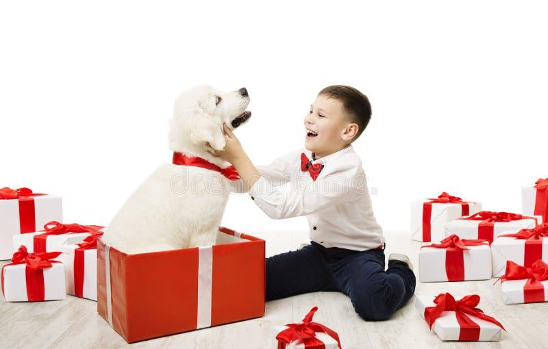Presente y niño, muchacho feliz del perro del niño con el regalo animal blanco del animal doméstico fotografía de archivo