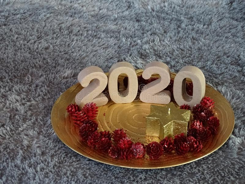2020 presented on golden plate. With star candle and red pineapples stock image