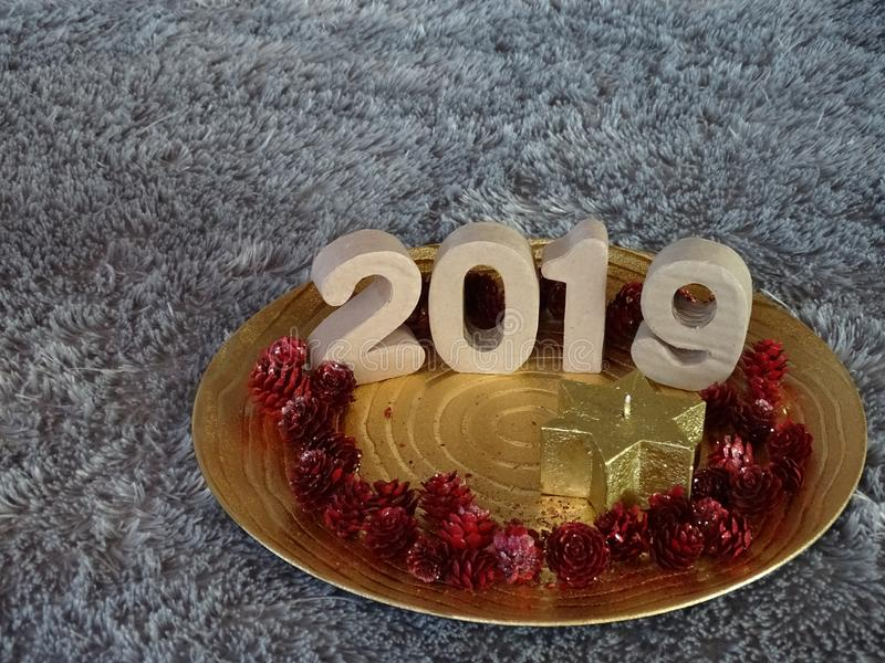 2019 presented on golden plate. With star candle and red pineapples stock photos