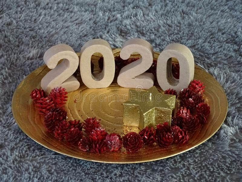 2020 presented on golden plate. With star candle and red pineapples royalty free stock photos