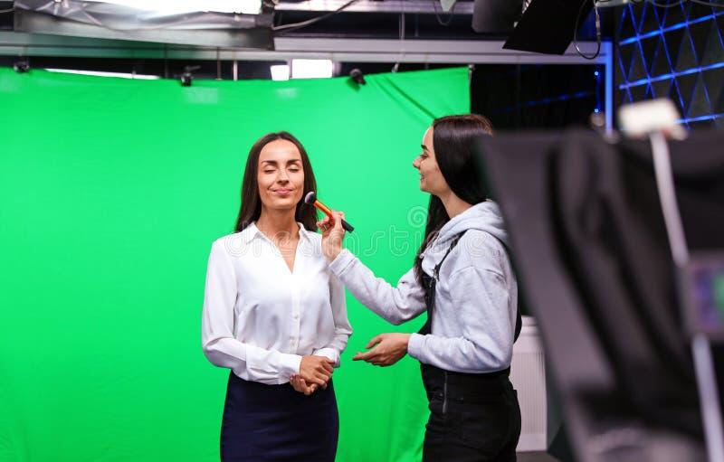 Presenter, makeup artist and video camera operator working. News broadcasting. Presenter, makeup artist and video camera operator working in studio. News stock photos