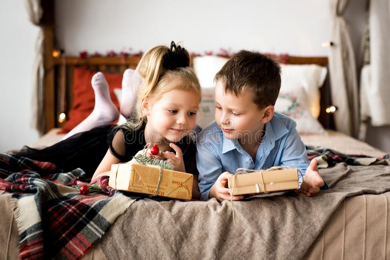 Presentes abertos da menina e do menino Feliz Natal e boas festas fotos de stock royalty free