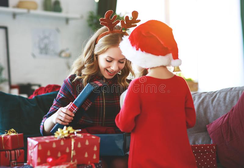 Presentes abiertos de la hija de la madre y del niño de la familia en la Navidad MES fotos de archivo