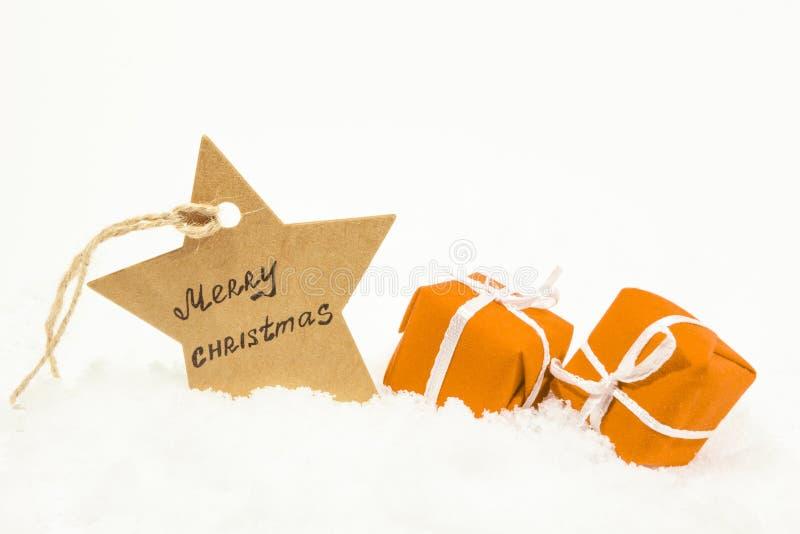 Presentes alaranjados na neve branca e em uma estrela com o Feliz Natal da inscrição imagem de stock