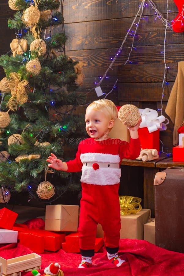 Presentes da abertura no Natal e no ano novo Criança feliz com um presente de Natal no fundo de madeira Criança do retrato com fotografia de stock royalty free