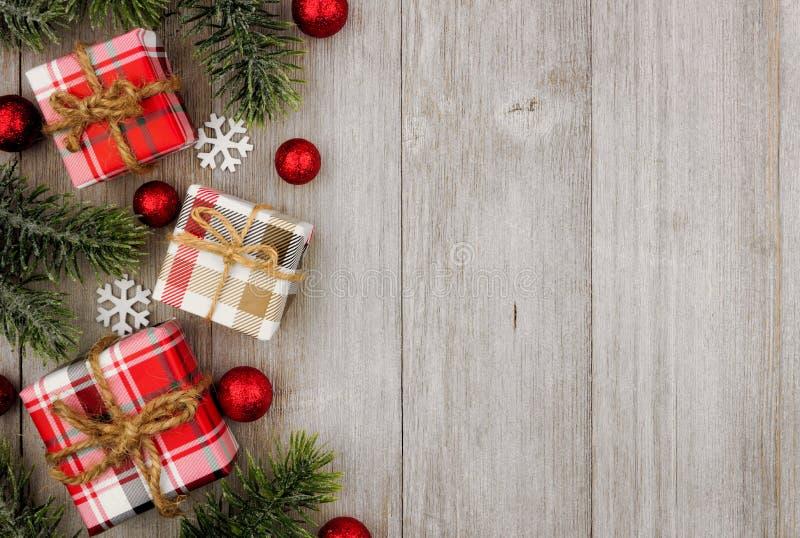 Presentes da beira do Natal e ramos de árvore laterais na madeira cinzenta imagem de stock