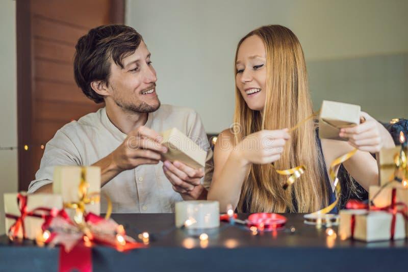 Presentes da embalagem do homem e da mulher Presente envolvido no papel do ofício com uma fita do vermelho e do ouro para o Natal fotos de stock