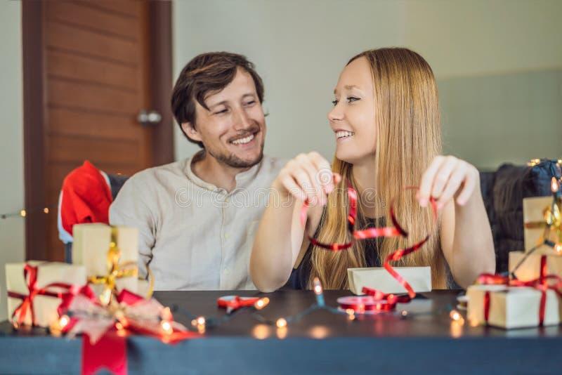 Presentes da embalagem do homem e da mulher Presente envolvido no papel do ofício com uma fita do vermelho e do ouro para o Natal fotografia de stock
