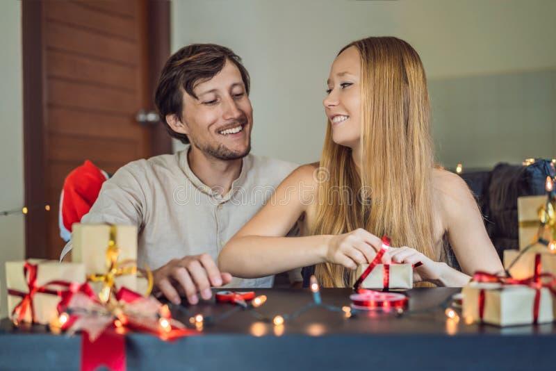 Presentes da embalagem do homem e da mulher Presente envolvido no papel do ofício com uma fita do vermelho e do ouro para o Natal foto de stock