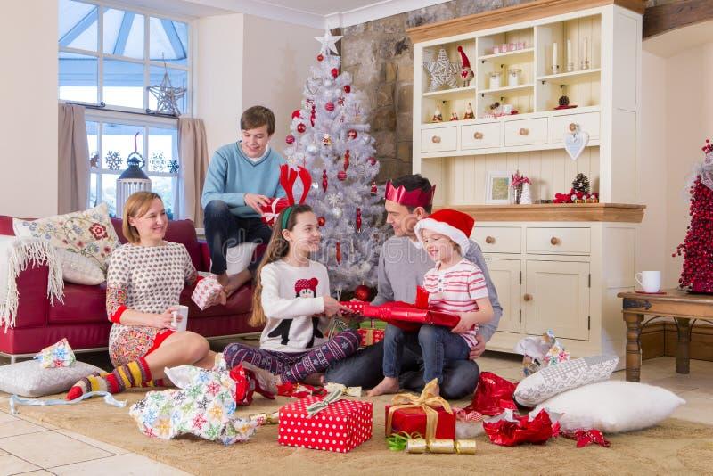Presentes de la abertura de la familia en el tiempo de la Navidad imagenes de archivo