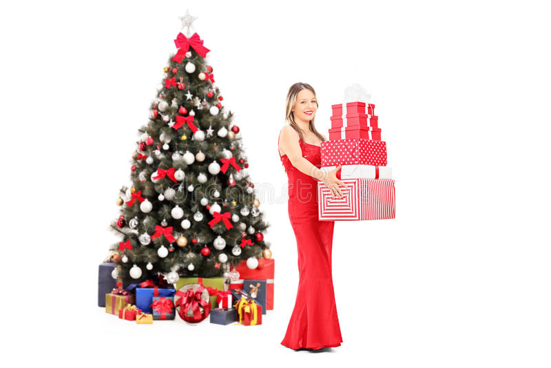 Presentes de la tenencia de la muchacha delante del árbol de navidad fotos de archivo libres de regalías