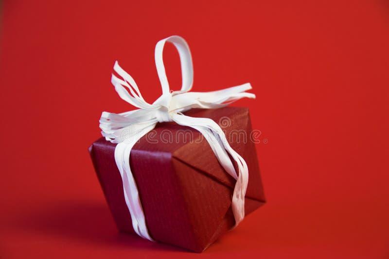Presentes de los regalos de la Navidad en fondo rojo Cajas de regalo envueltas simples, clásicas, rojas y blancas con los arcos d imagen de archivo libre de regalías