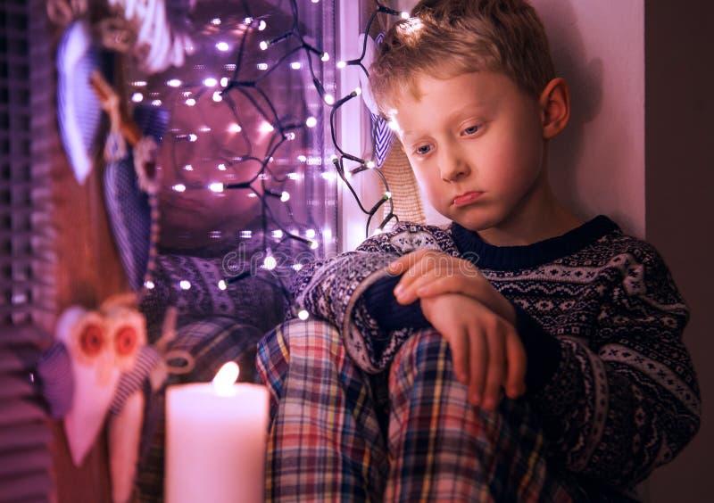 Presentes de Natal de espera do rapaz pequeno triste imagens de stock