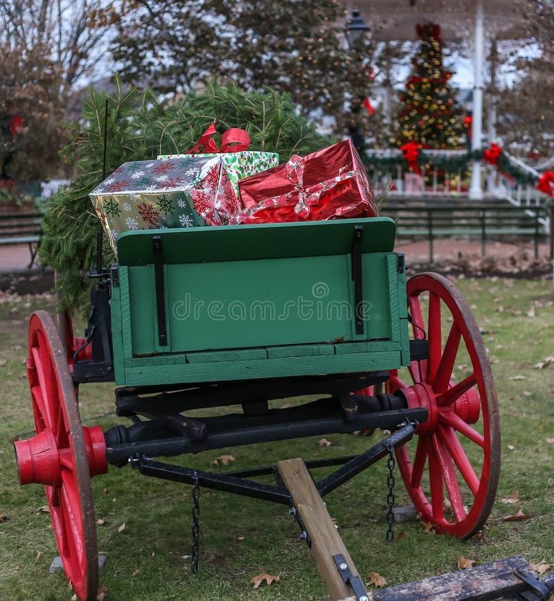 Presentes de Natal no vagão antigo com a árvore de Natal borrada no backround fotografia de stock