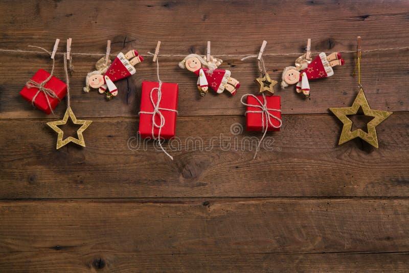 Presentes de Natal vermelhos com os anjos dourados que penduram em uma madeira velha imagens de stock royalty free