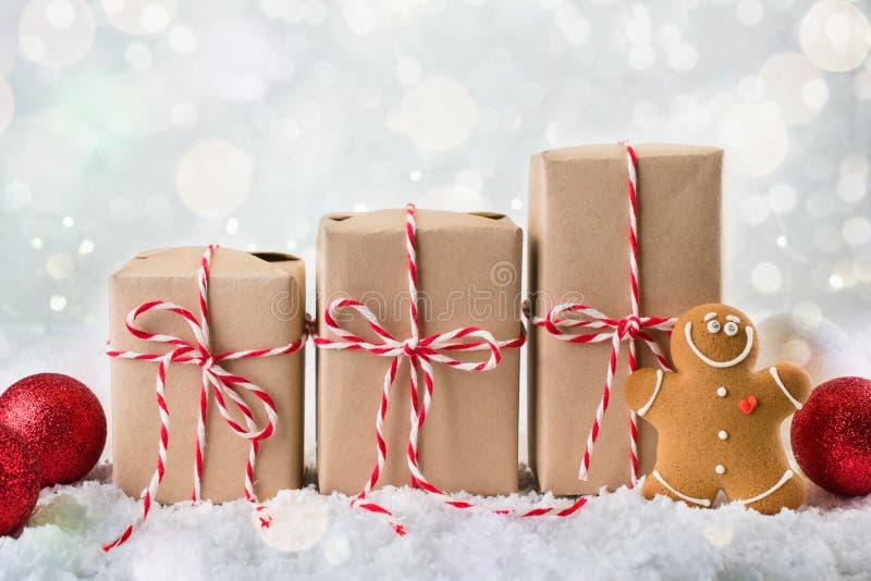Presentes do Natal da embalagem Três caixas de presente do Natal envolvidas no papel de embalagem amarrado com corda vermelha e b foto de stock