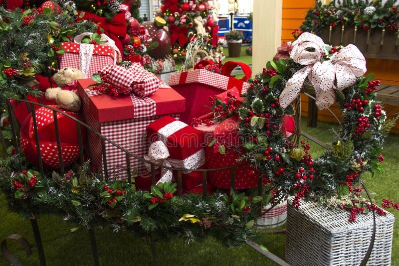 Presentes do Natal dentro do trenó, com flores e a árvore decorada imagens de stock royalty free