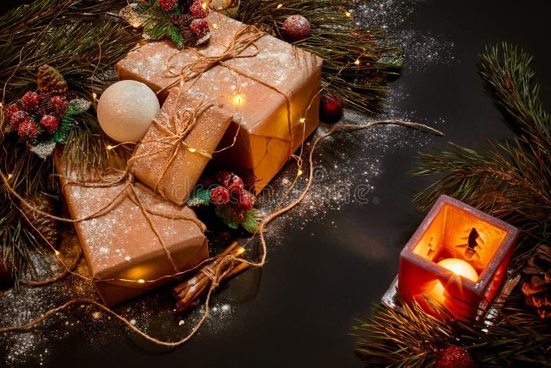 Presentes do Natal e castiçal vermelho perto do ramo spruce verde em um fundo preto Fundo do Natal Vista superior fotos de stock royalty free