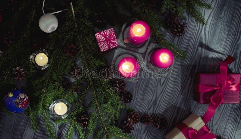 Presentes do Natal e velas ardentes em uma sala escura imagem de stock