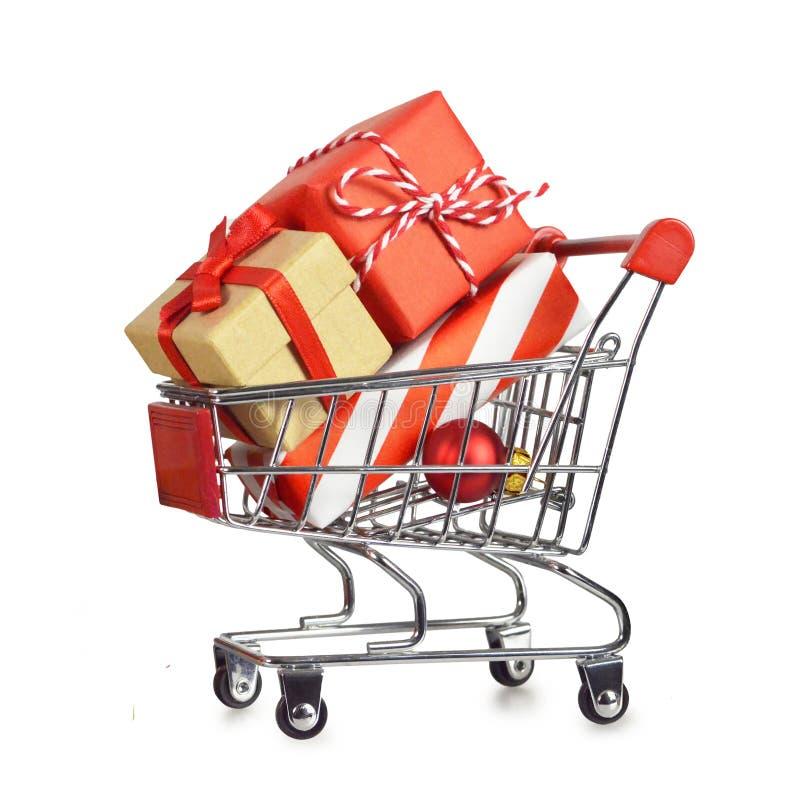 Presentes do Natal no carrinho de compras isolado no branco imagem de stock