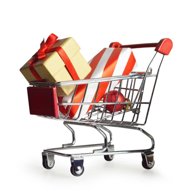 Presentes do Natal no carrinho de compras isolado no branco fotografia de stock