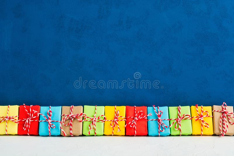 Presentes do Natal no papel colorido em uma linha com fundo azul imagens de stock
