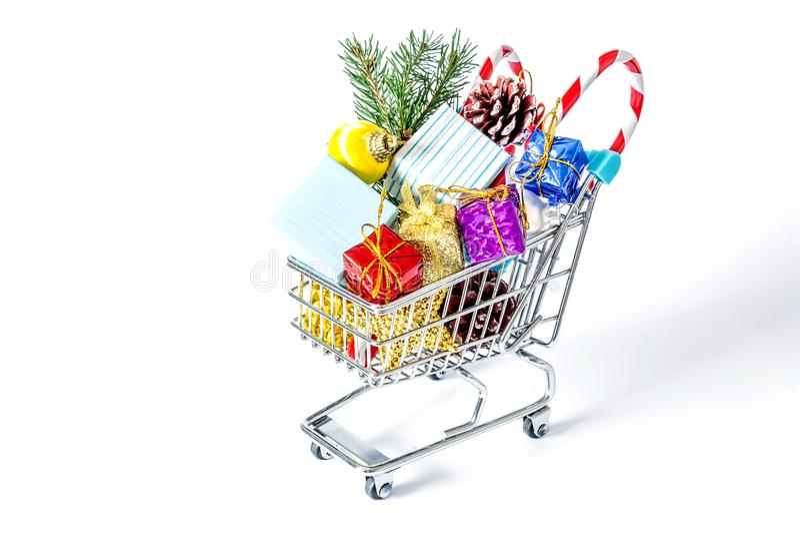 Presentes do ` s do ano novo em um close-up do trole da compra isolados foto de stock