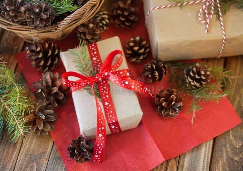 Presentes e cones do Natal e em uma tabela de madeira imagem de stock