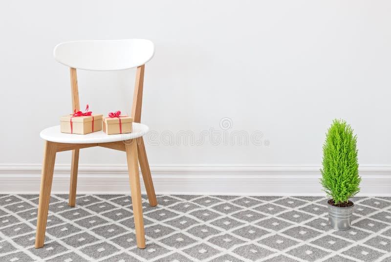 Presentes en una silla blanca, y poco árbol verde foto de archivo